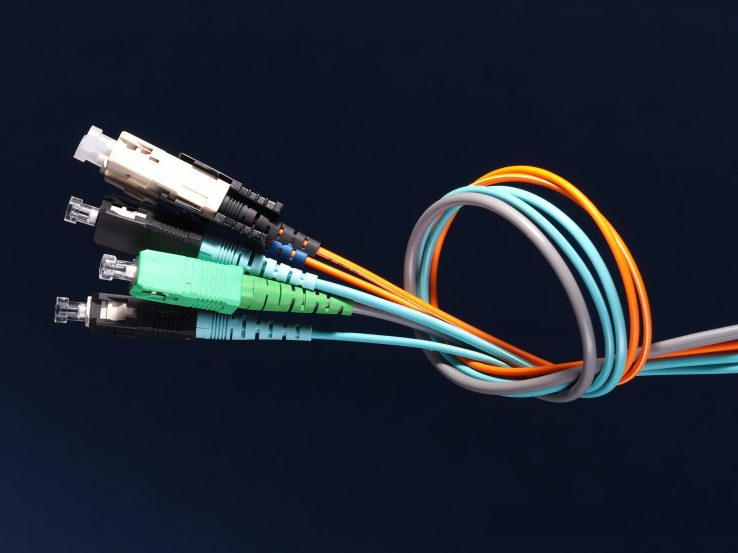 A bundle of three fiber optic patch cords with connectors arranged in a knot on black background, Australia 2015