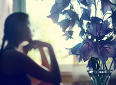 A silhouette of the young woman sitting at the window